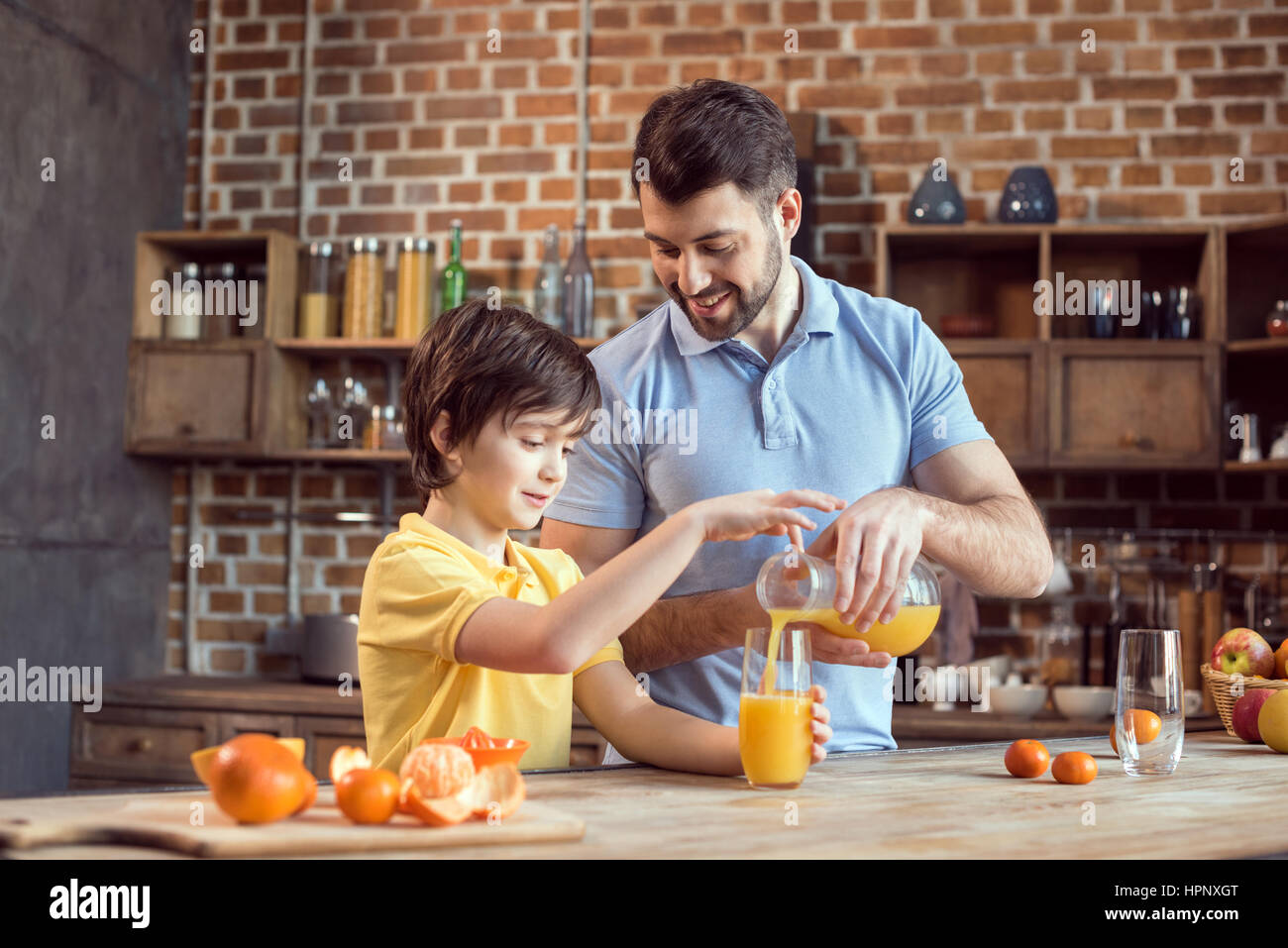 father and son pouring fresh juice in glass - Stock Image