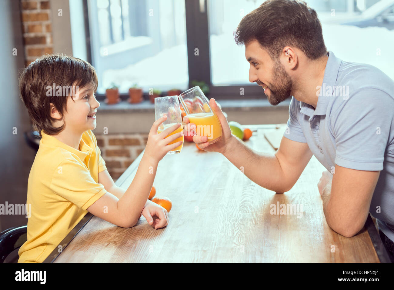 happy father and son drinking fresh juice together - Stock Image
