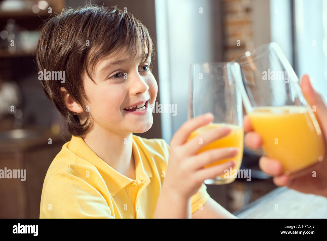 little boy and father clinking glasses with fresh juice - Stock Image
