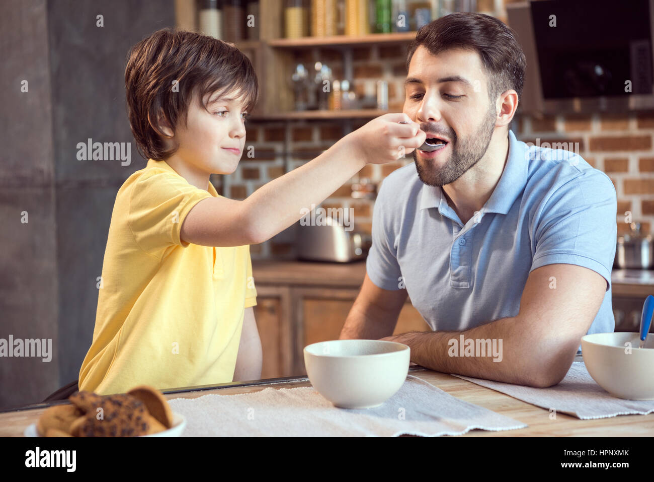 smiling boy feeding father with breakfast - Stock Image