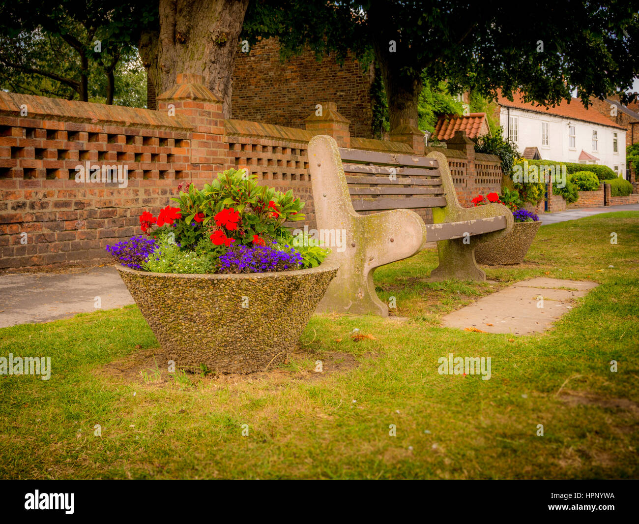 Pre-cast concrete flowerpot with flowering plants and concrete / wood bench seat outdoors, Haxby, Yorkshire, UK. - Stock Image