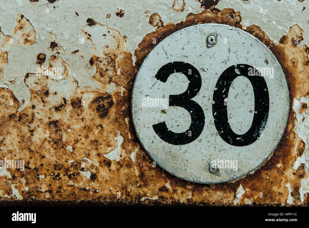 The number 30 on a metals disc with rusty background - Stock Image