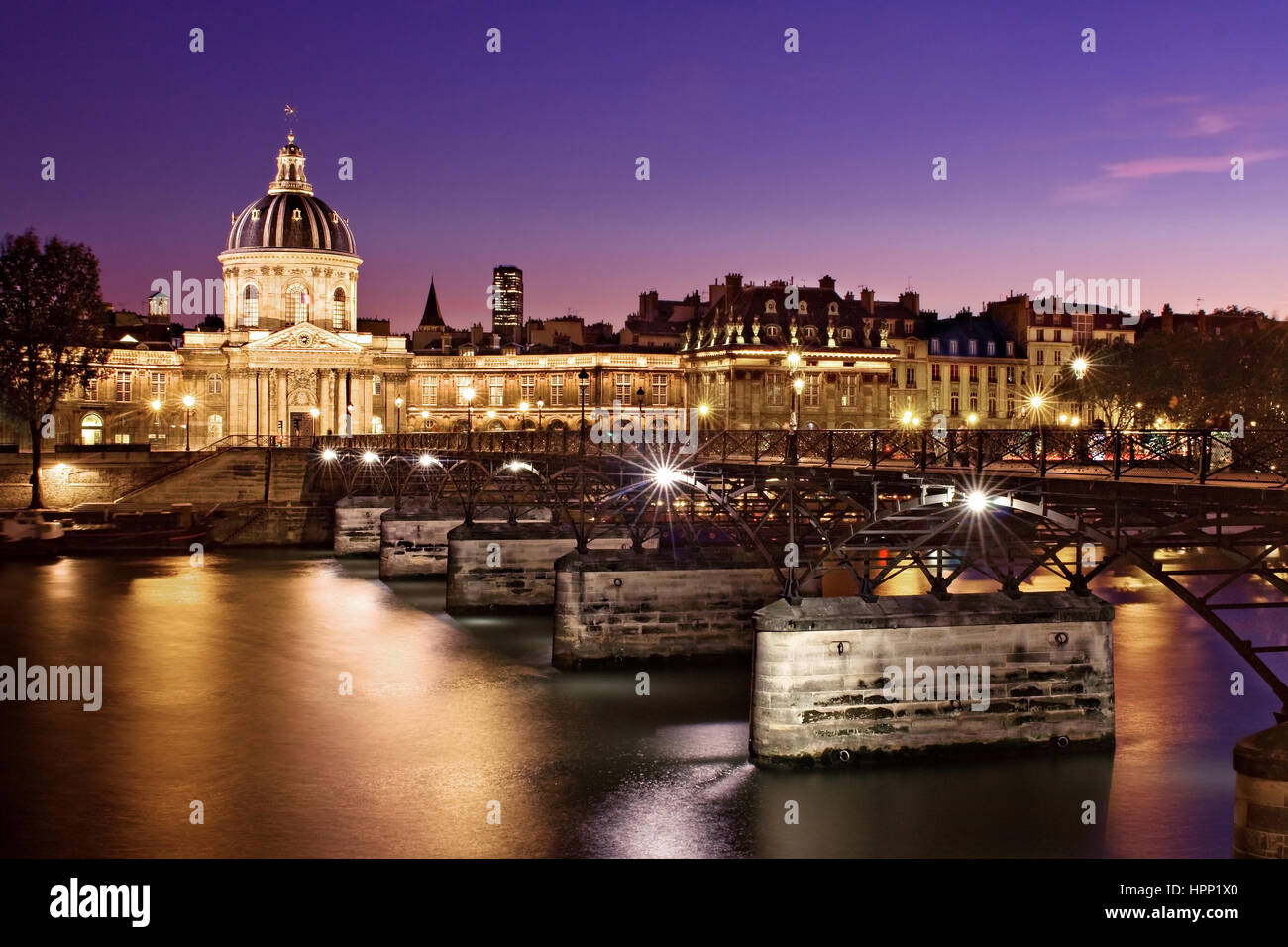 Night view of the Pont des Arts on the River Seine in Paris, France. The domes building of the Institut de France - Stock Image