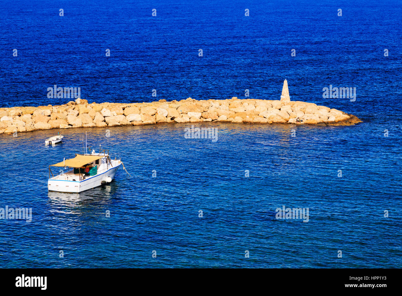 Boat and fisherman in Agios Georgios Harbour, Paphos, Cyprus. - Stock Image