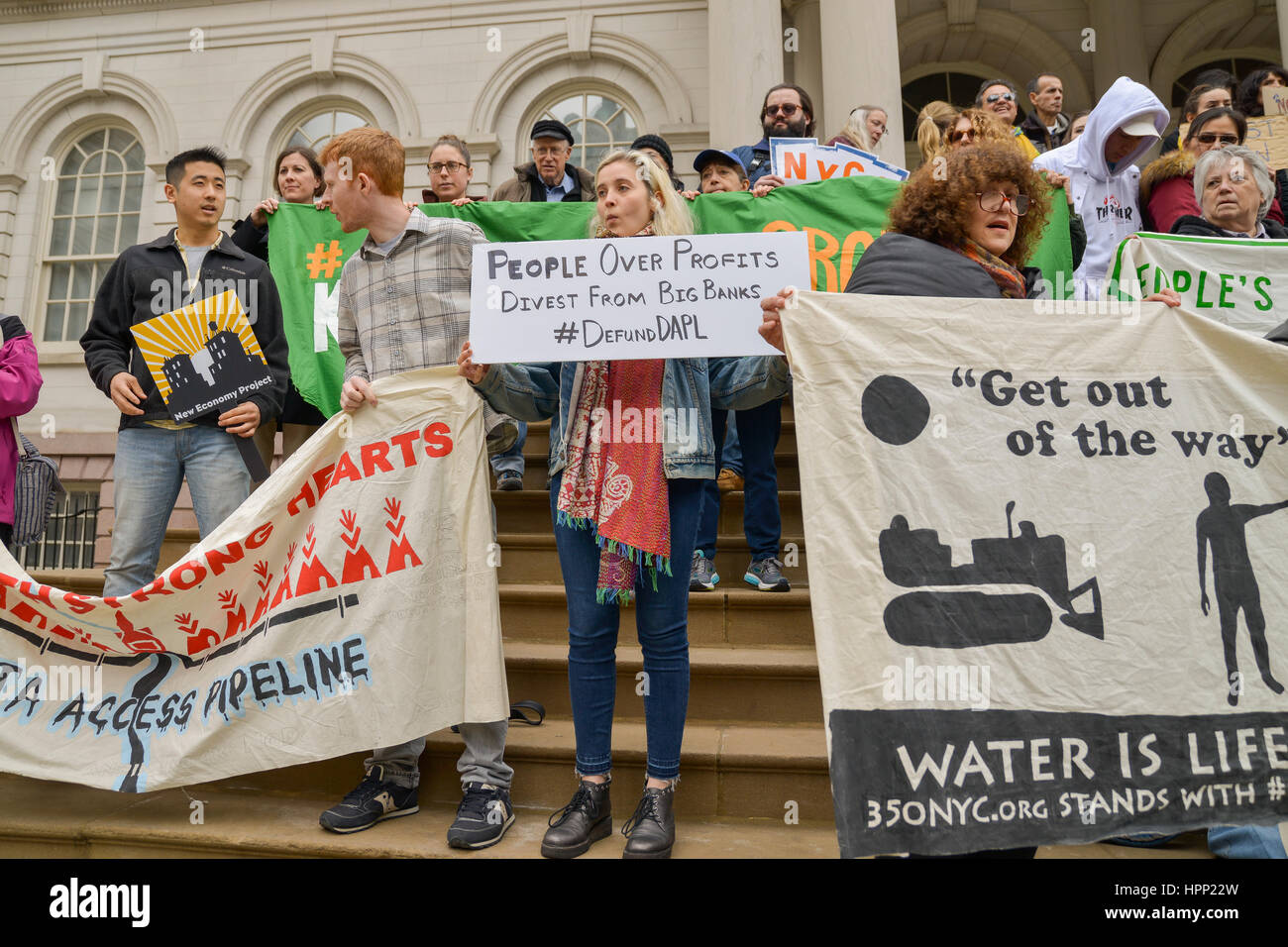 New York, United States. 23rd Feb, 2017. Demonstrators hold signs while rallying on the steps of City Hall. Activists - Stock Image