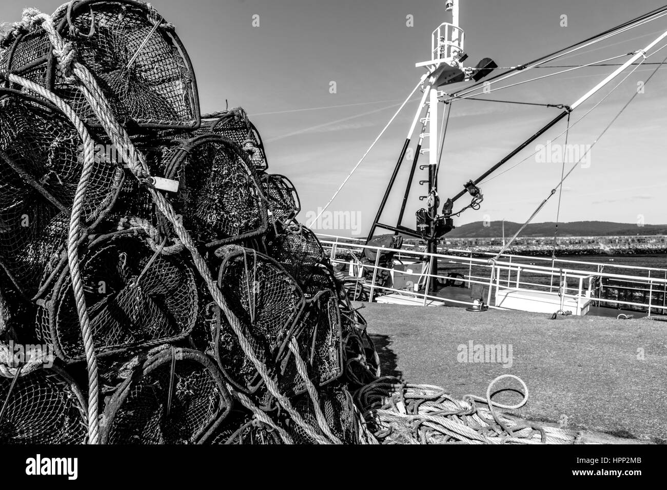 Pile of Fishing Traps Against Moored Fishing Ship in Harbour - Stock Image