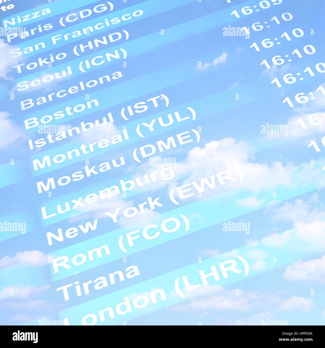 Flight information board against blue sky with clouds - Stock Image