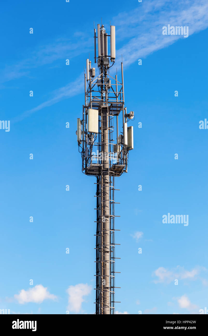 Telecommunication tower for mobile phone with antennas over a blue sky. Distribution function of contract mobile - Stock Image