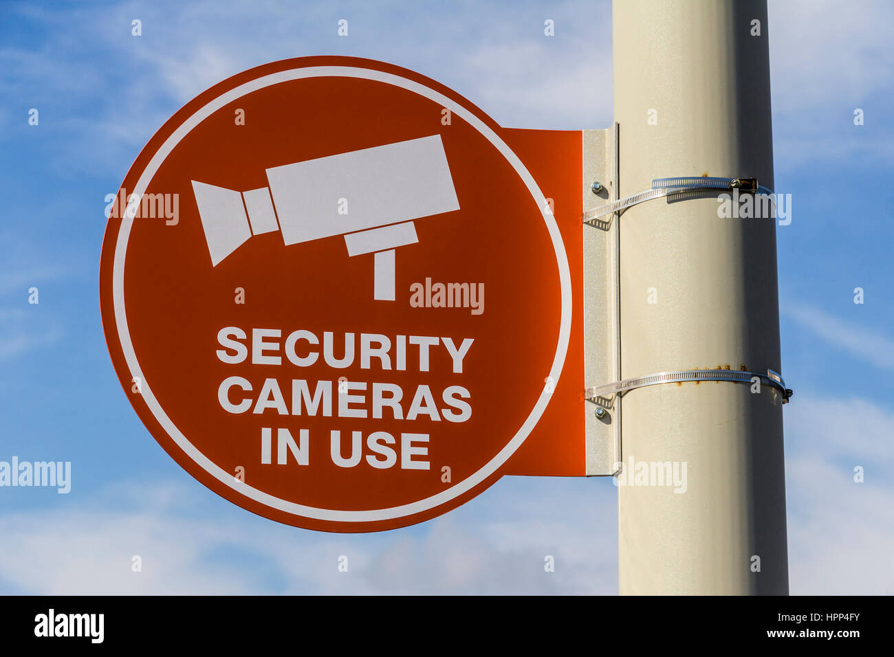 Orange Security Camera In Use Sign on Gray Post and Partly Sunny Background  I - Stock Image