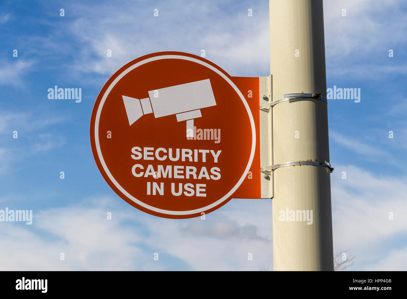 Orange Security Camera In Use Sign on Gray Post and Partly Sunny Background  II - Stock Image