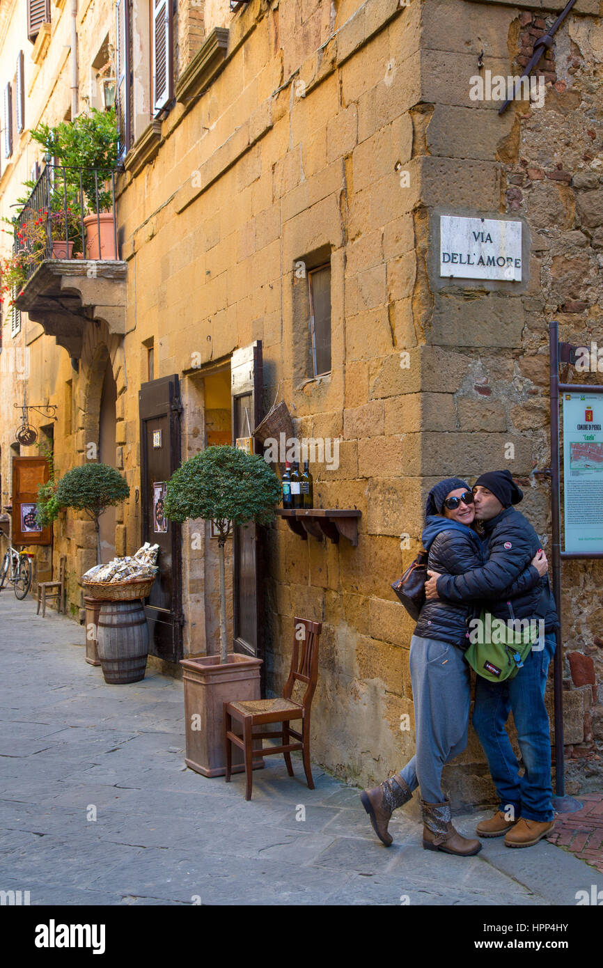 Couple kissing below Via Dell Amore road sign in Medieval town of Pienza, Tuscany, Italy - Stock Image