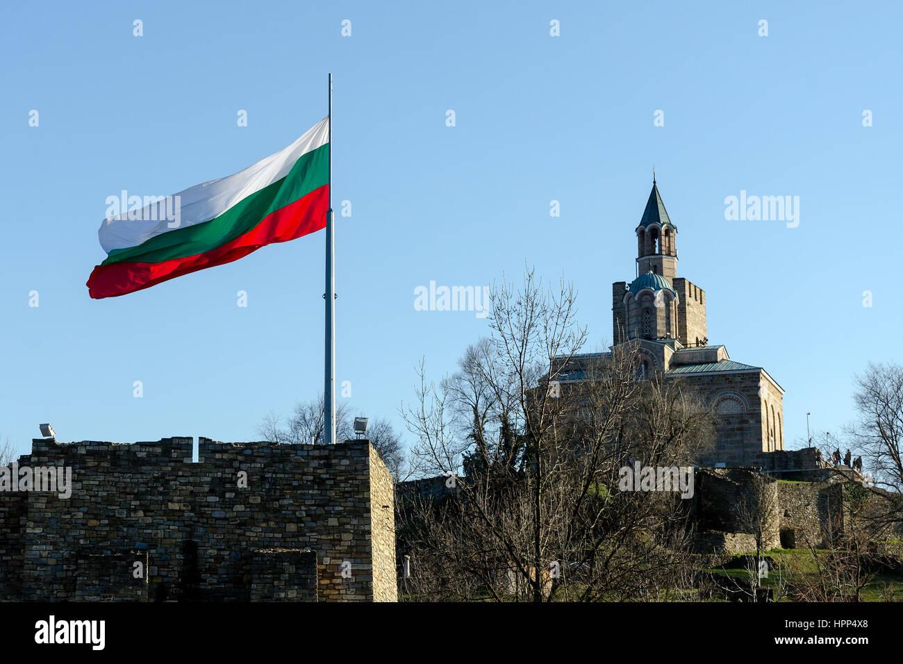 Waving Bulgarian flag at Tsarevets fortress with patriarch church in background, Veliko Tarnovo, Bulgaria Stock Photo