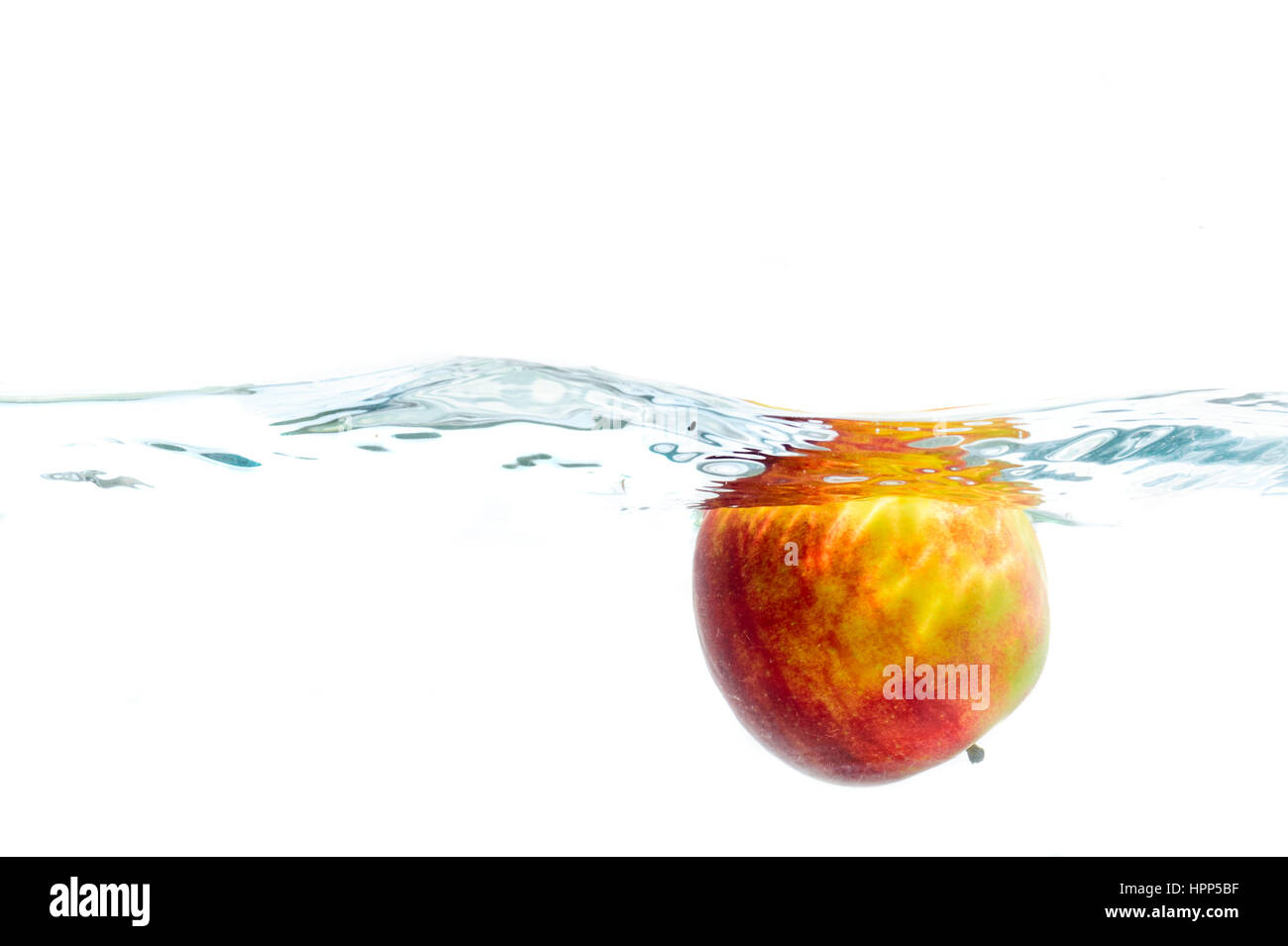 Fresh fruits immersed in clear water, studio shot on white background - Stock Image