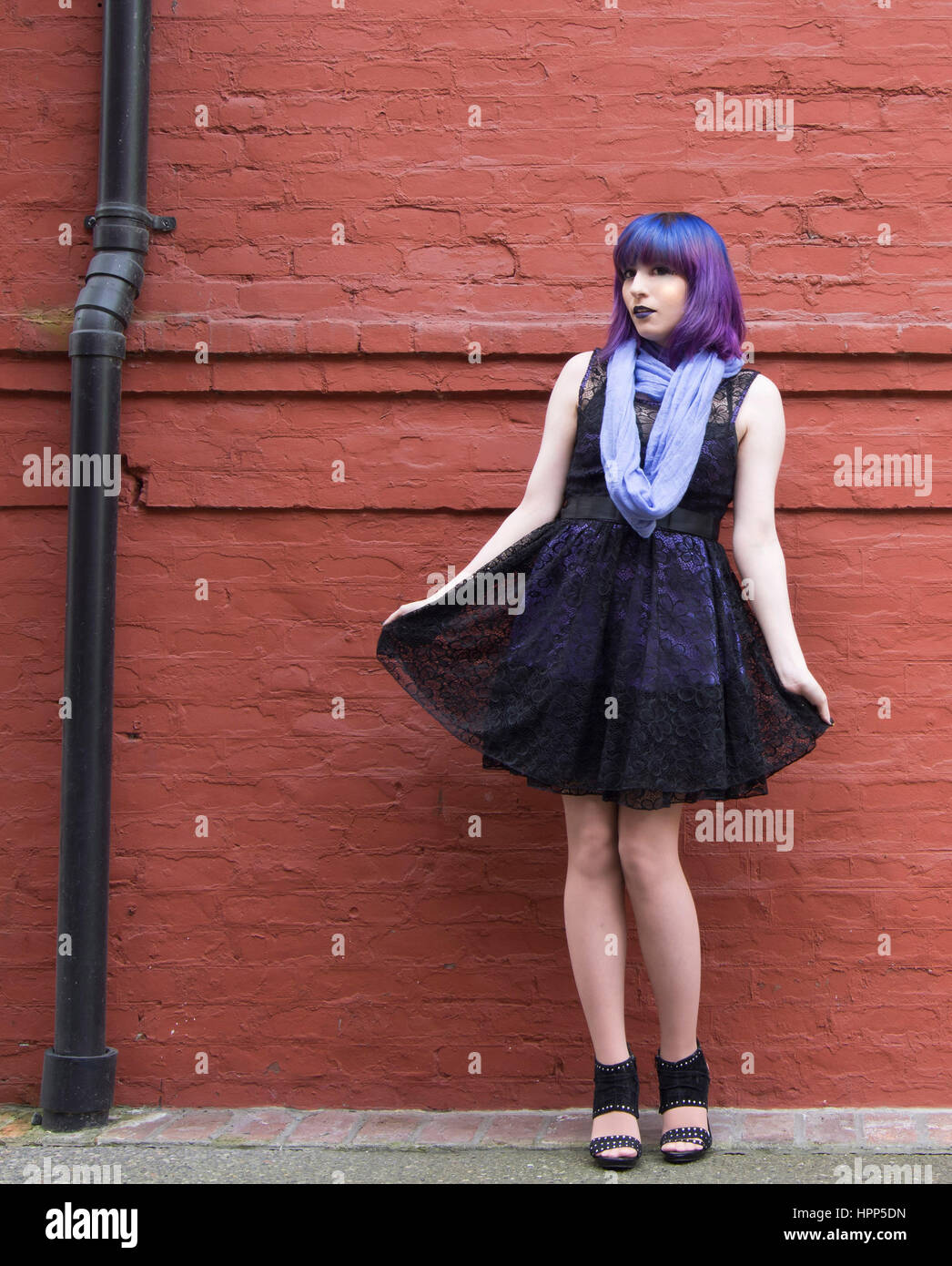alternative, sassy woman wearing black dress, multi colored hair, red brick wall backgound - Stock Image