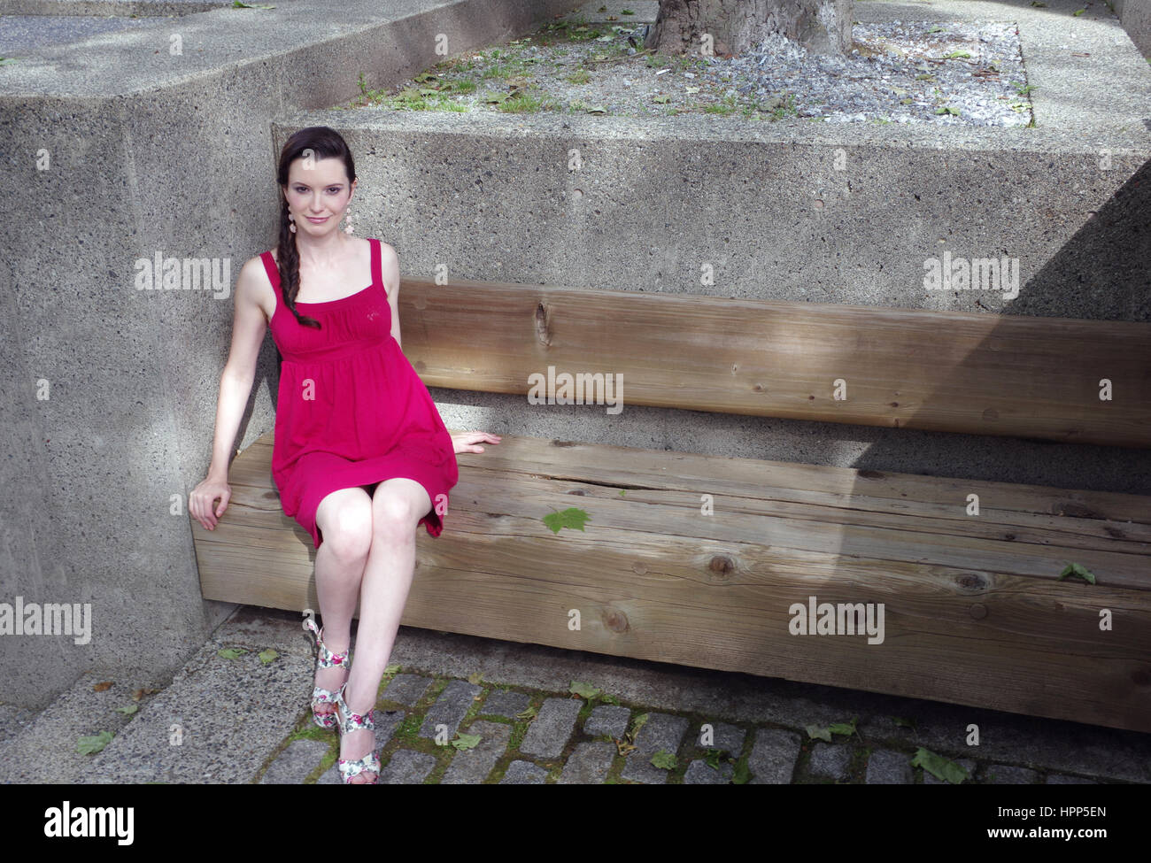woman wearing red dress lounging on a bench in the sun in the city - Stock Image