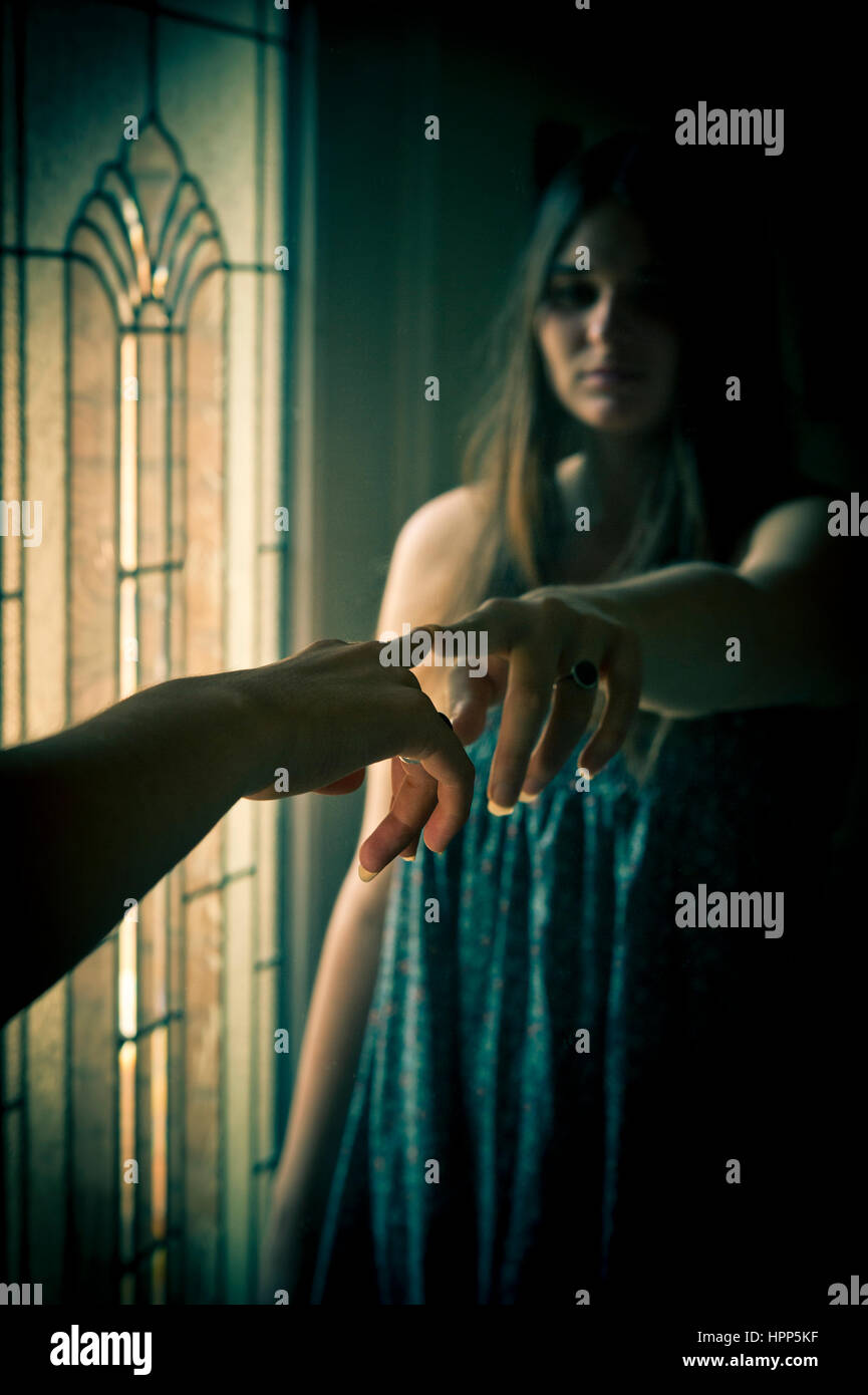 Young woman pointing finger at her reflection in the mirror - Stock Image