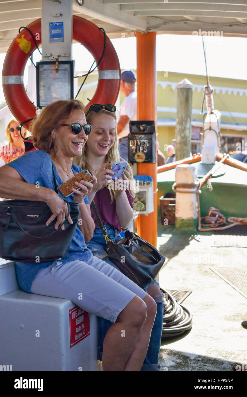 A mother and daughter laughing and smiling while using cell phones on a Florida tour boat with a life preserver - Stock Image