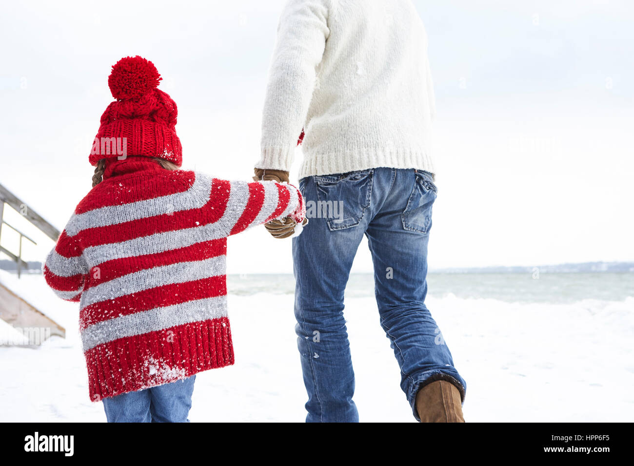 Father and daughter walking in the snow, rear view - Stock Image