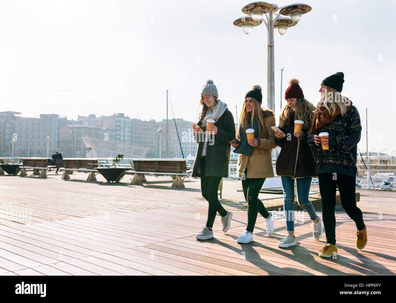 Four friends with coffee to go and cell phones walking on promenade in winter - Stock Image