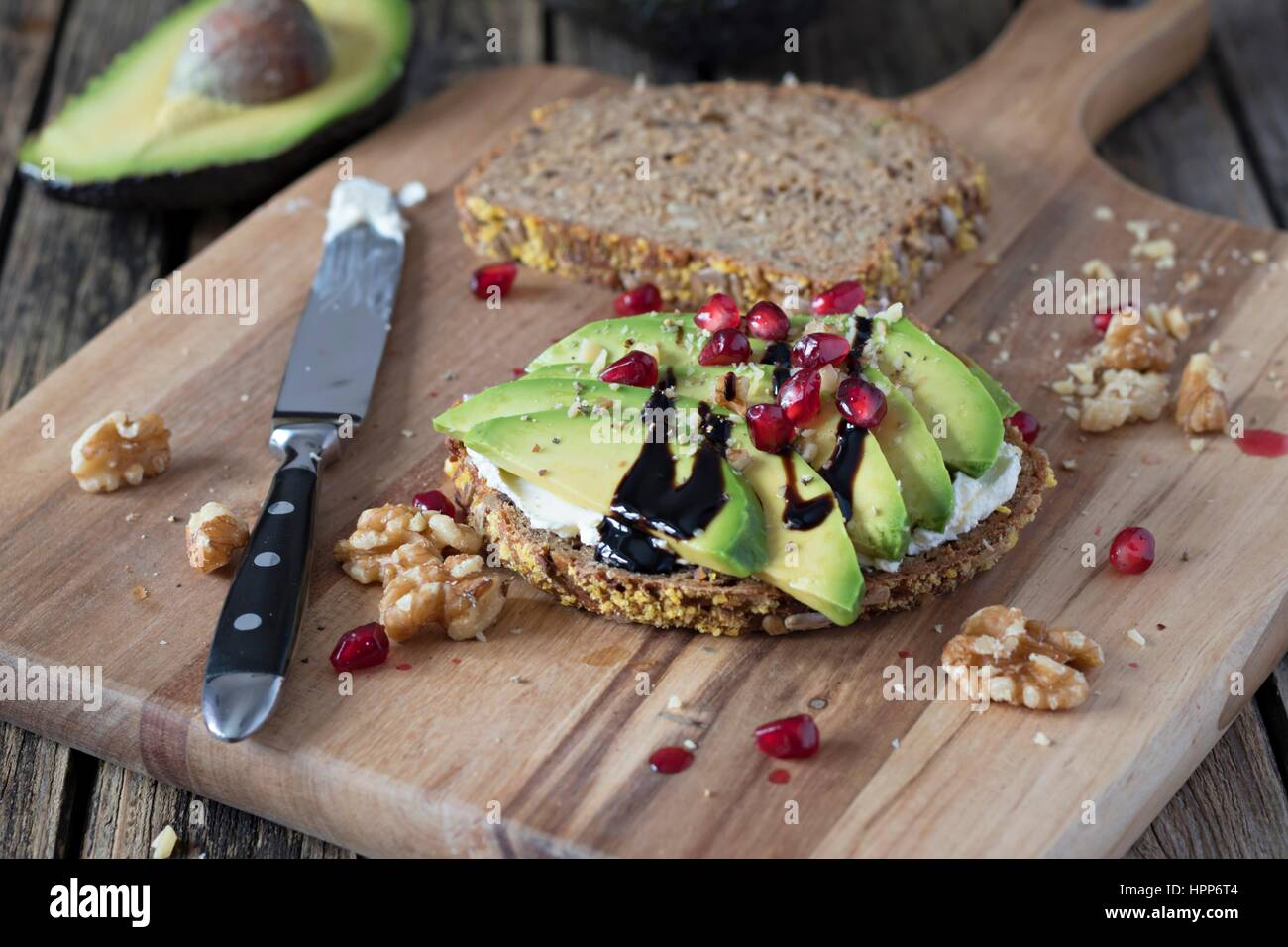 Protein bread slice with cream cheese, sliced avocado, walnuts and  pomegranate seed on wooden board - Stock Image