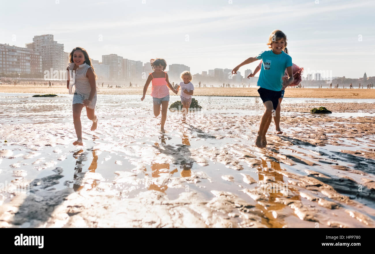 Group of five children running together on the beach - Stock Image