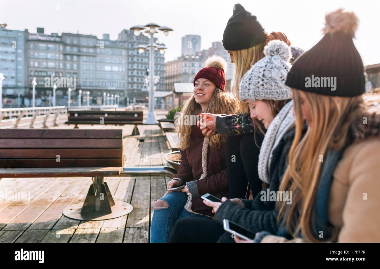 Spain, Gijon, four friends using their cell phones outdoors - Stock Image