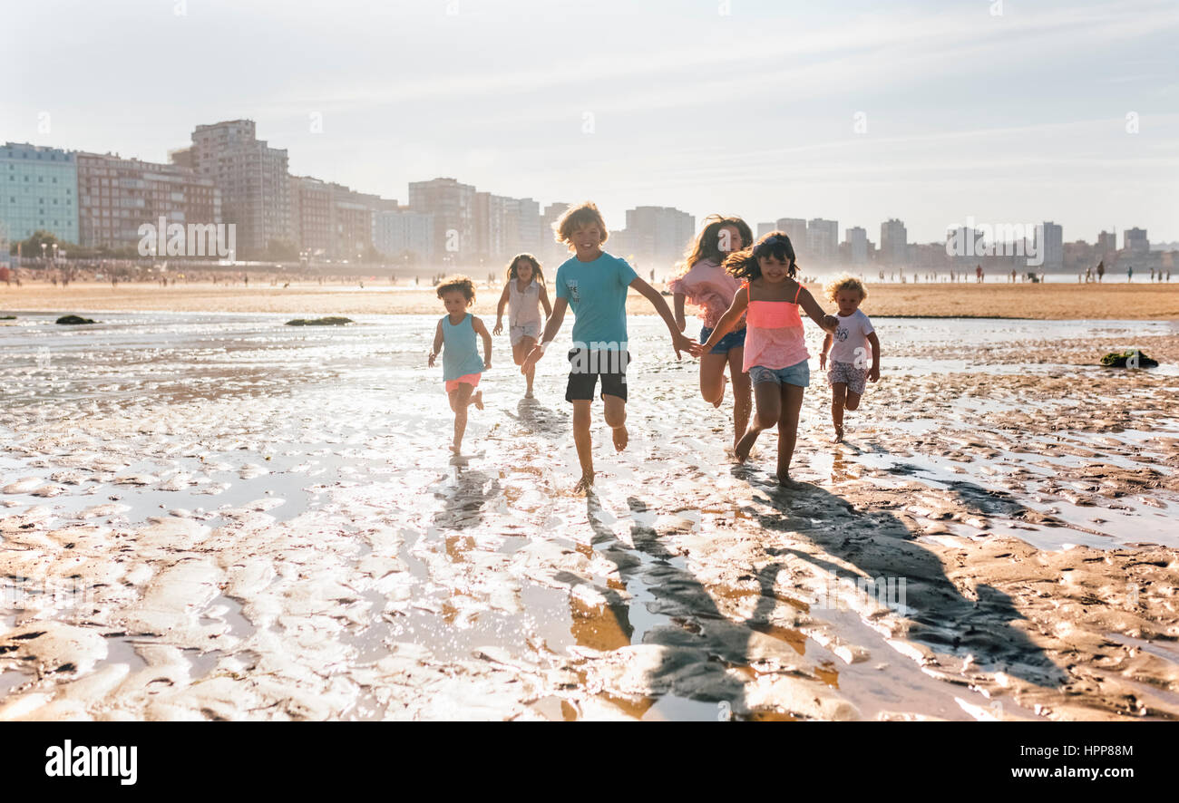Group of six children running together on the beach - Stock Image