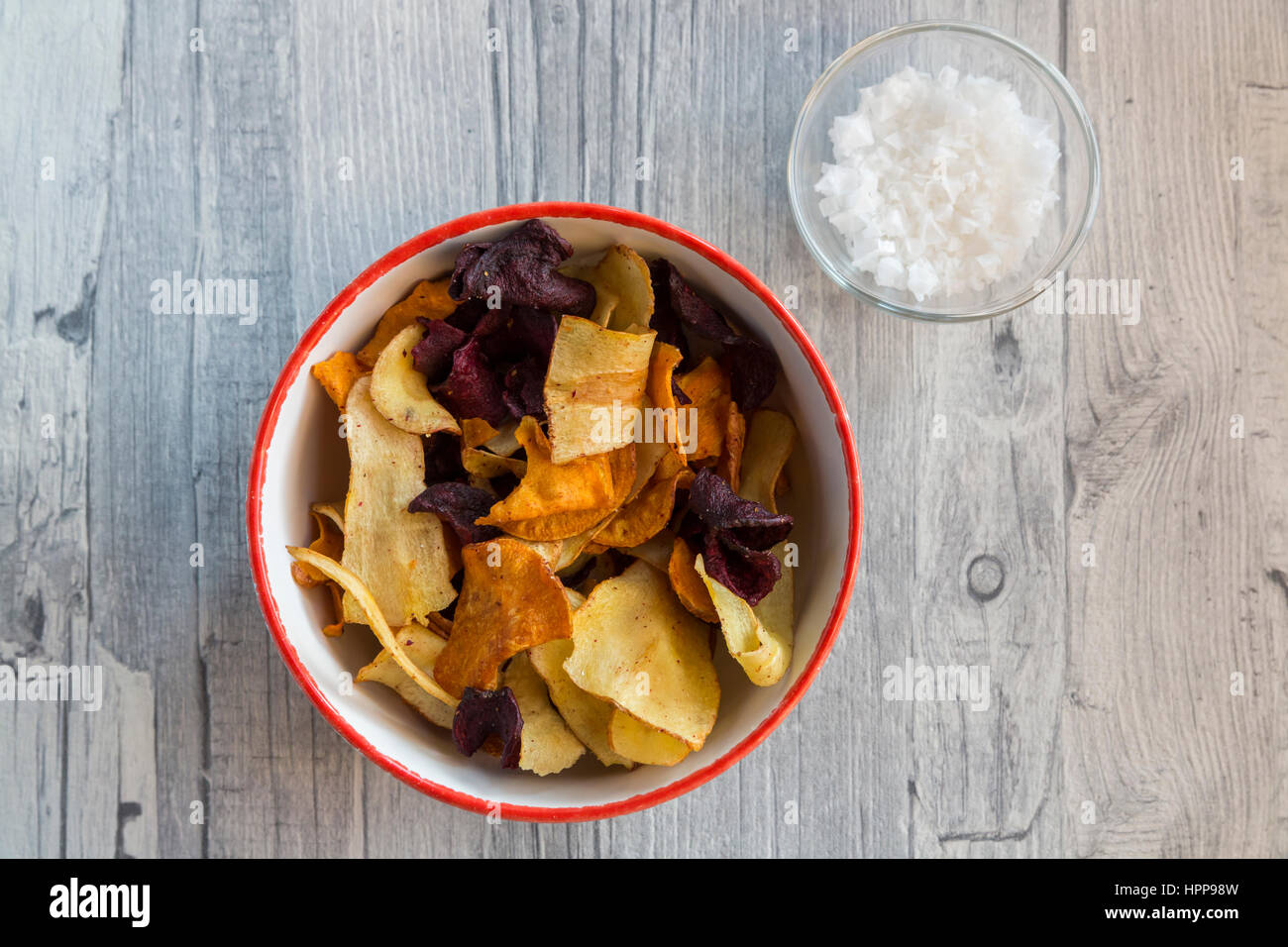 Vegetable chips and pyramide salt in bowls Stock Photo