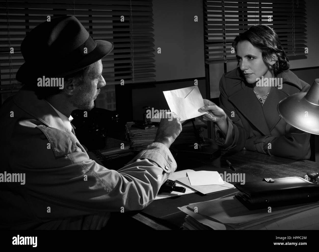 Woman handing over an envelope to a detective at police station, 1950s film noir style. - Stock Image