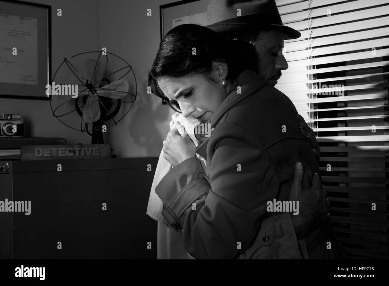 Detective consoling and hugging a young woman in his office, film noir scene. - Stock Image