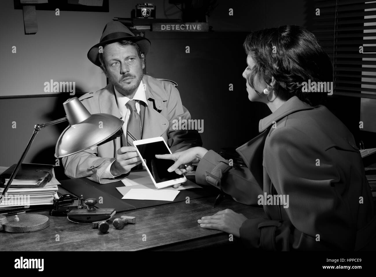Woman touching detective's tablet sitting at his office desk. - Stock Image