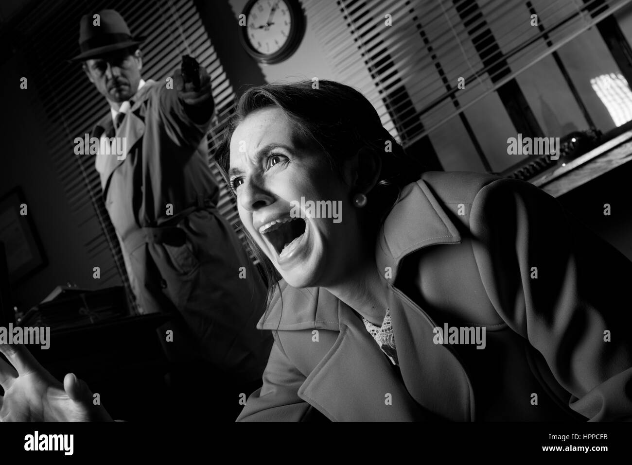 Detective standing in the dark and pointing a gun to a screaming woman. - Stock Image