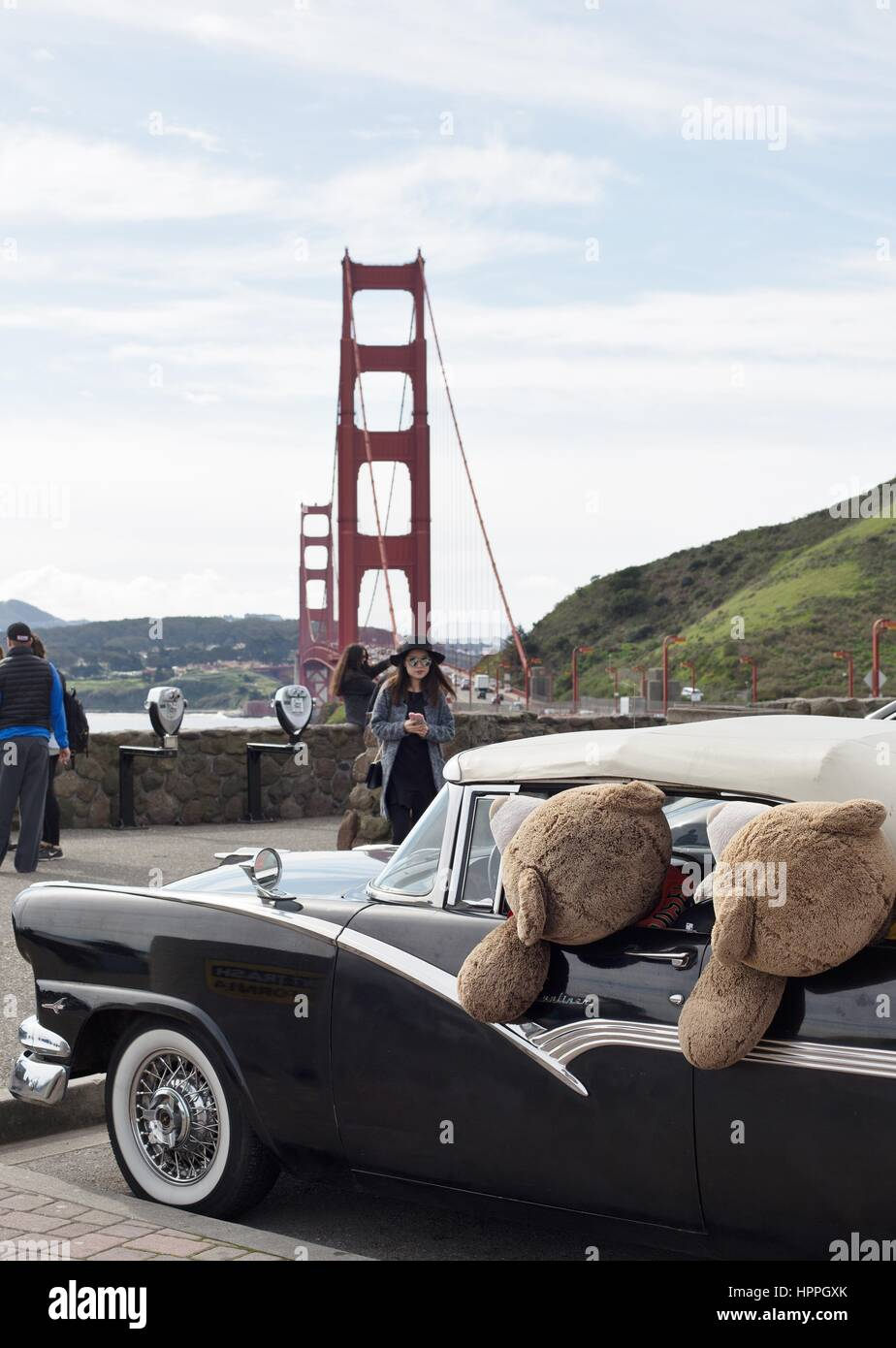 A tourist taking a picture of a vintage car full of giant teddy bears at the observation area of Golden Gate bridge - Stock Image