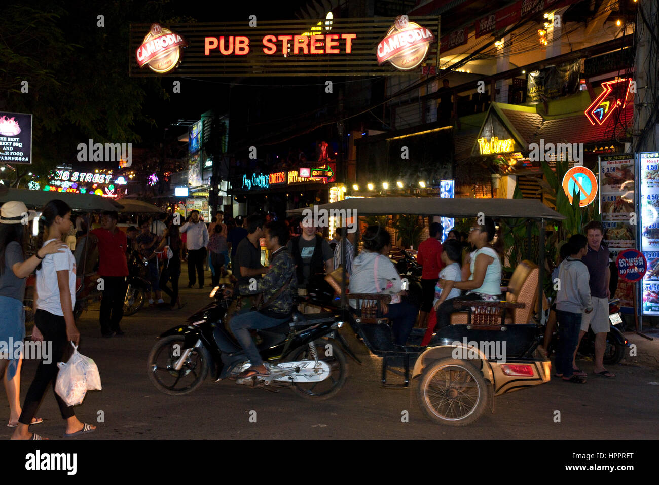 Busy street scene in Siem Reap, Cambodia, looking down 'Pub Street' with mopeds, locals, tourists and tuk - Stock Image