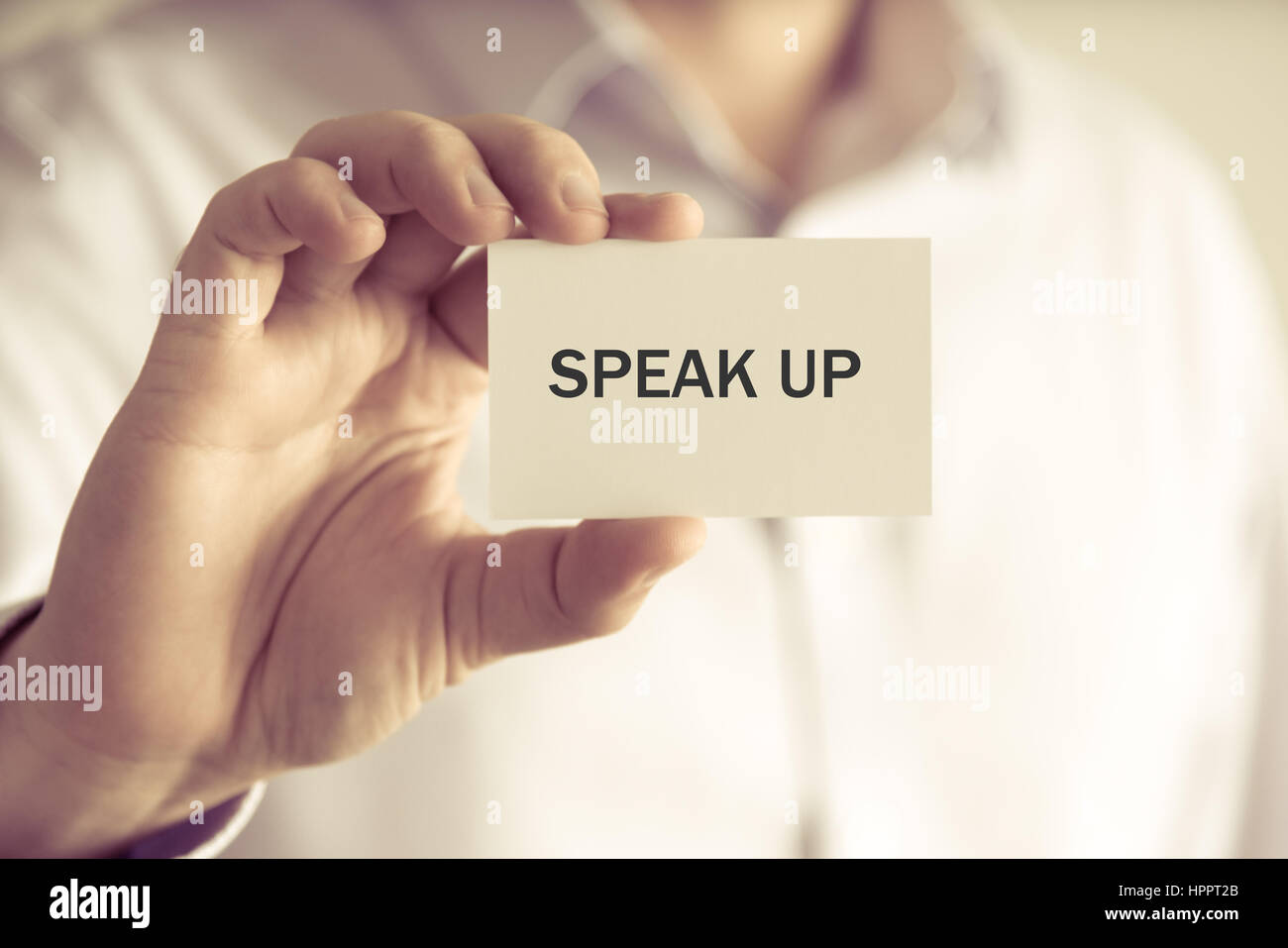 Closeup on businessman holding a card with text SPEAK UP, business concept image with soft focus background and - Stock Image