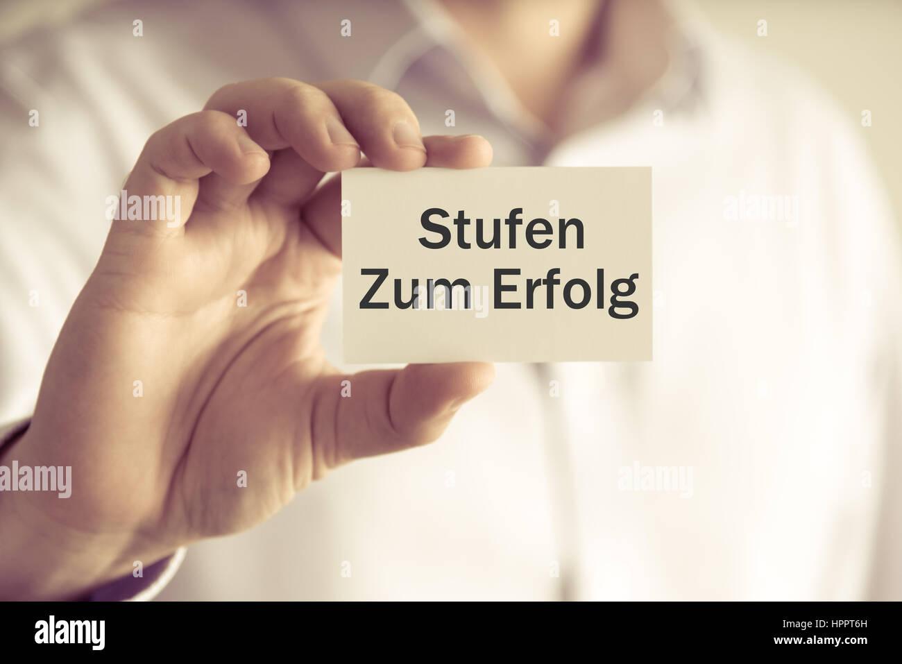 Closeup on businessman holding message card 'Stufen Zum Erfolg' written in German - translation : Steps - Stock Image