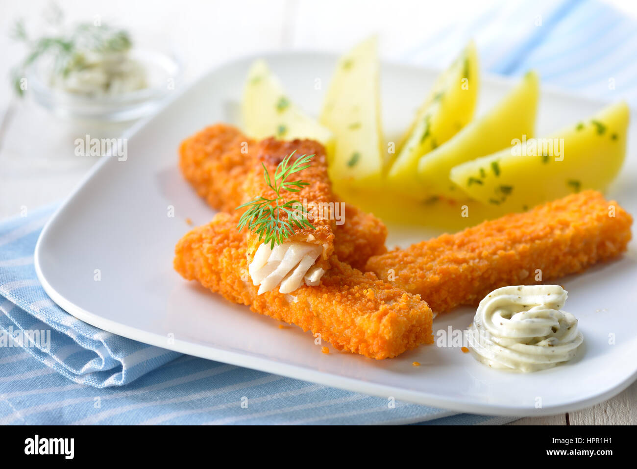 Crispy fish fingers of breaded pollack fillet served with parsley potatoes and remoulade sauce on a white plate - Stock Image