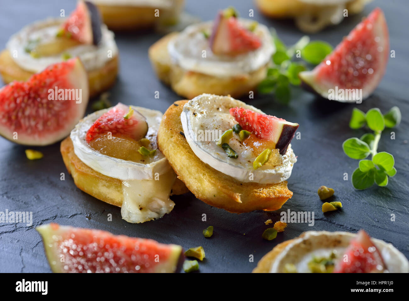 Baked spicy crostini appetizers with goat cheese, fig mustard, pistachios and fresh figs served on a slate board - Stock Image