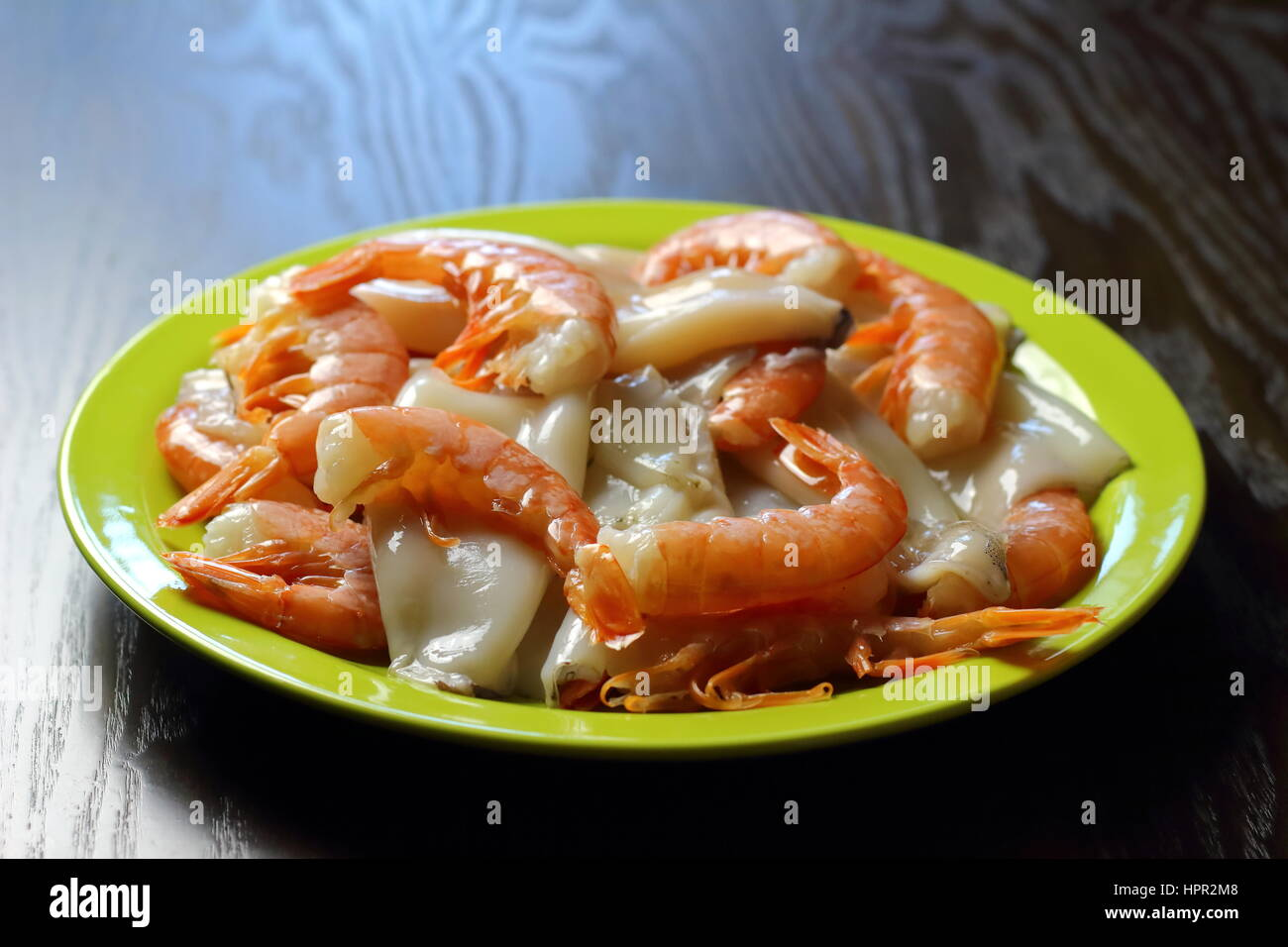 Raw (uncooked) shrimps (prawns) and squid in green dish lying on dark wooden table - Seafood recipe ingredients - Stock Image