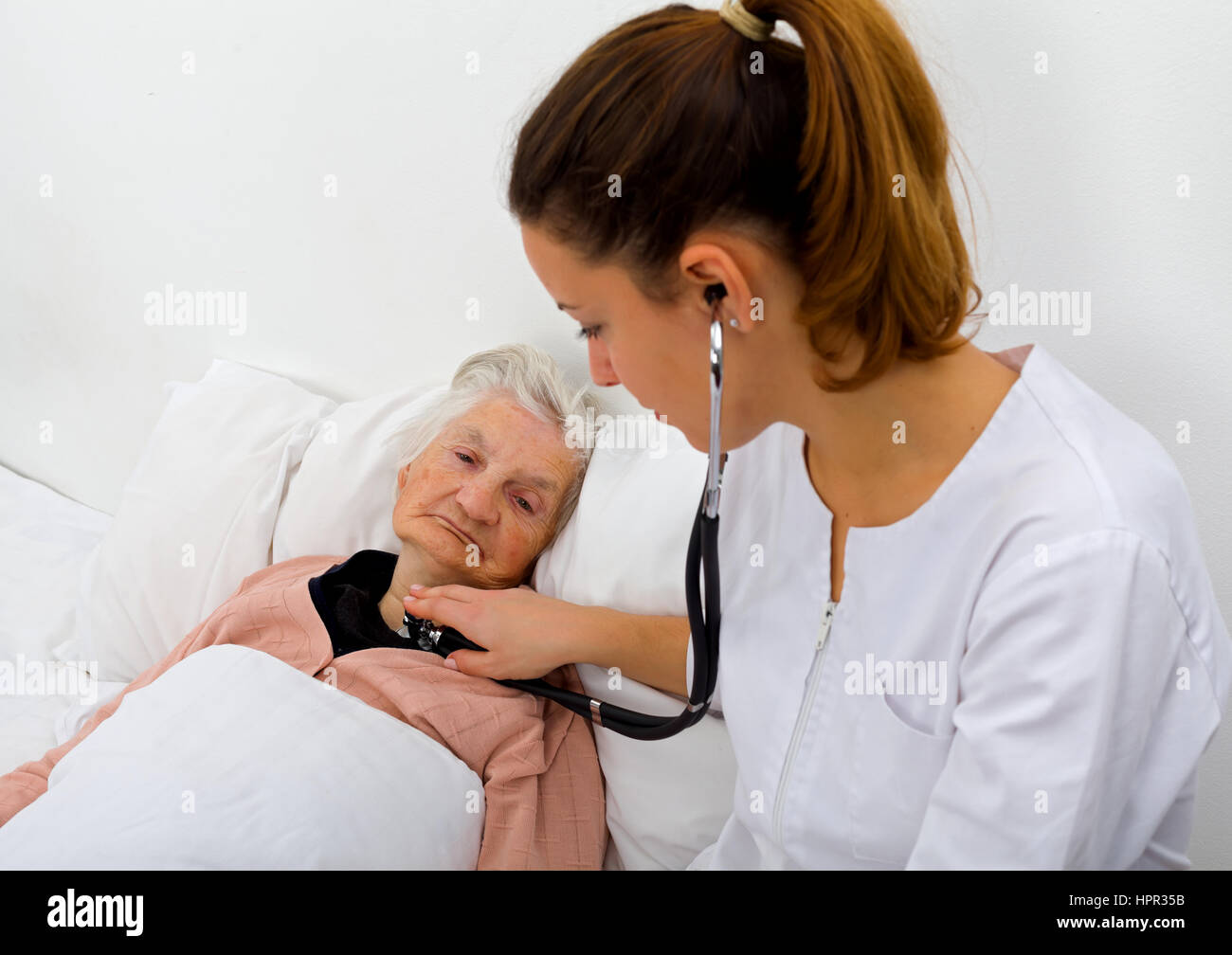 Elderly woman with her caregiver at home - Stock Image