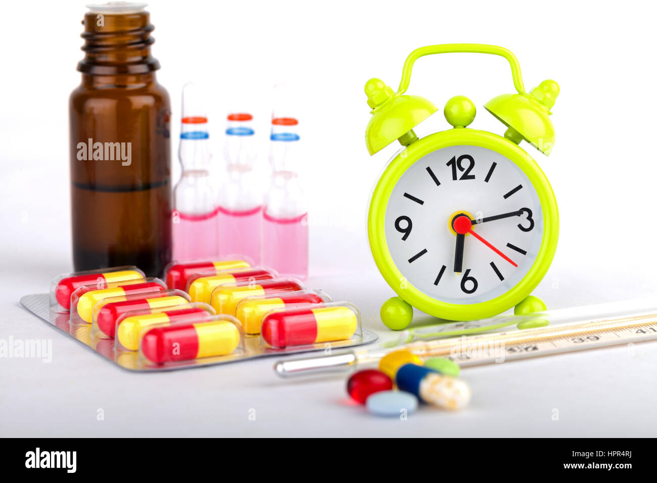 Picture of a green clock, colourful pills and capsules - Stock Image