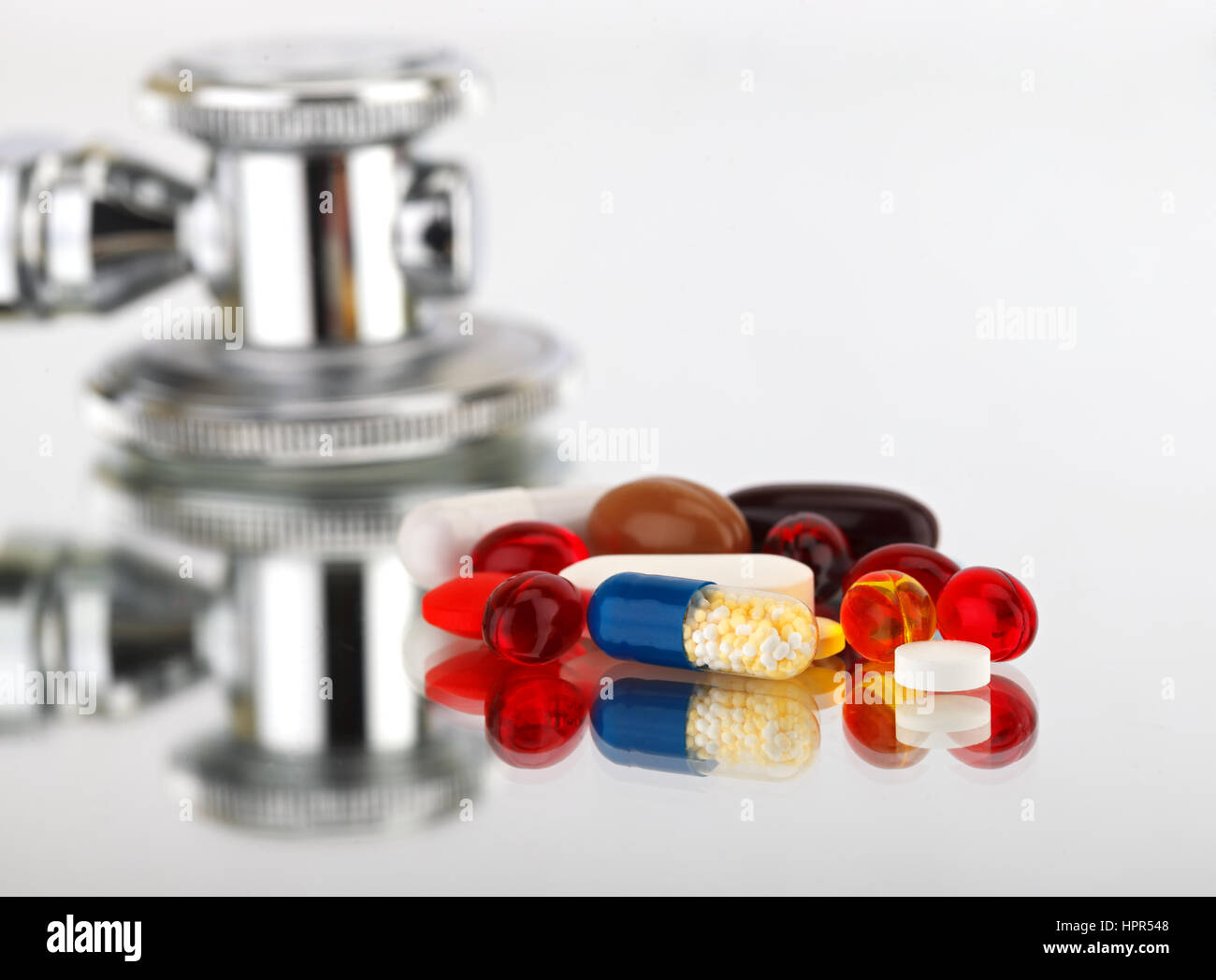 Picture of a colourful pills capsules and stethoscope - Stock Image