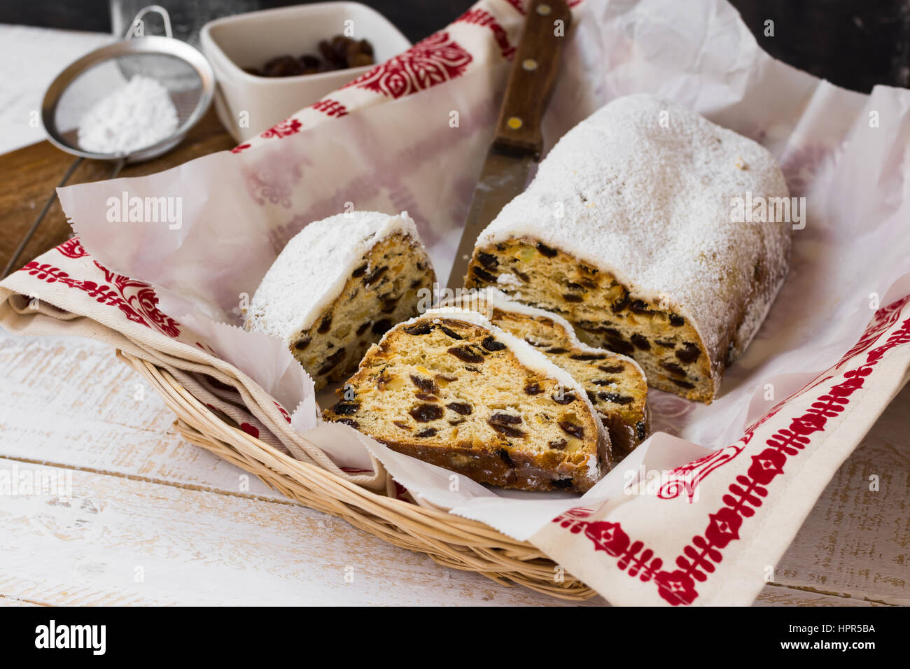 Christmas stollen cut into slices in wicker basket with ornamented towel ingredients, sieve with caster sugar, on - Stock Image