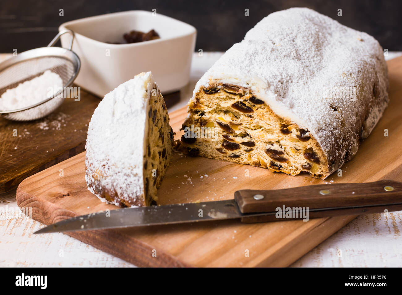 Homemade Christmas stollen cut off piece on wood board with knife, ingredients, sieve with powder, close up - Stock Image