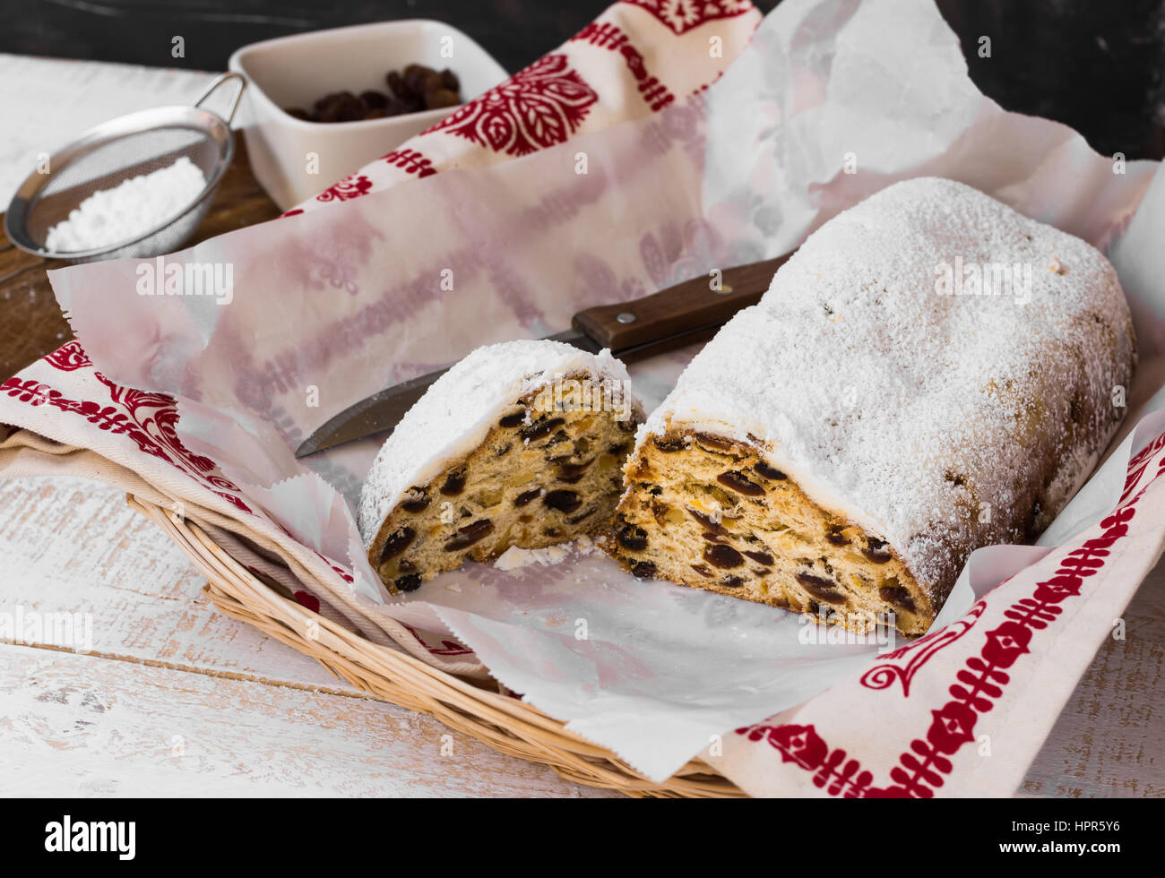 Christmas stollen powdered, with cut off piece with knife, in wicker basket, ingredients, kitchen towel, top view, - Stock Image