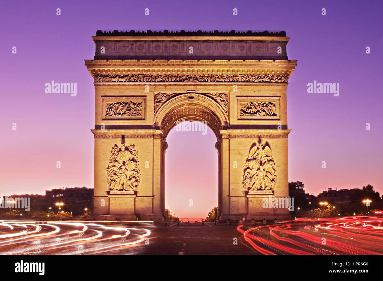 A dawn view of the Arc de Triomphe taken from the Avenue de la Grande Armee. The light trails of traffic lead to - Stock Image