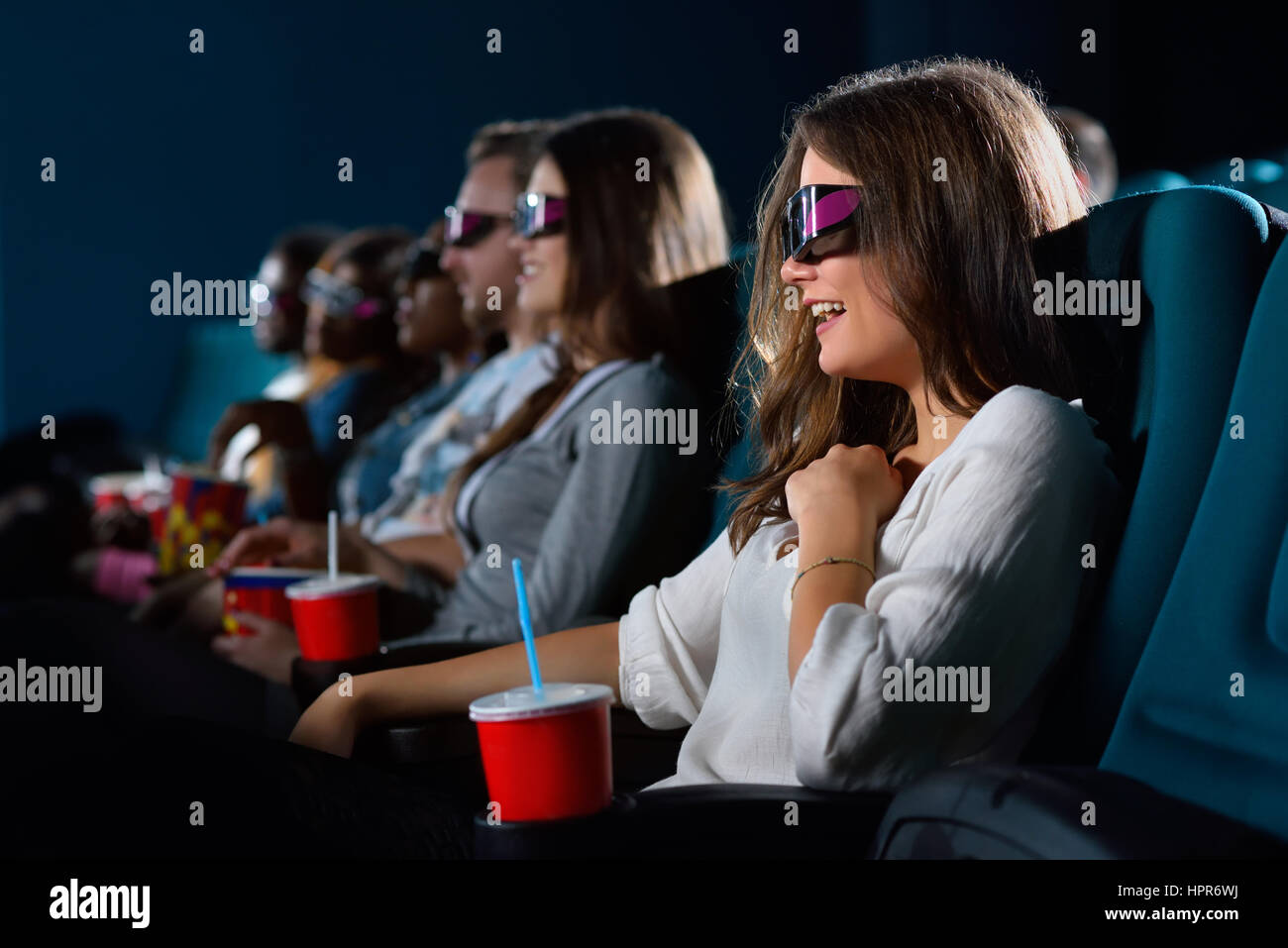 Her new favorite comedy. Cropped closeup shot of a cheerful young woman laughing while enjoying a comedy movie at - Stock Image