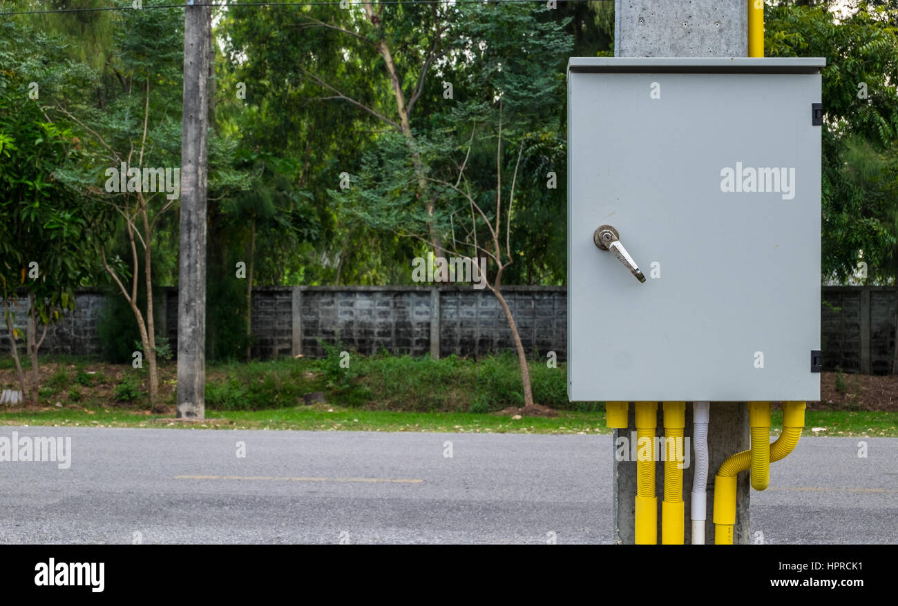 Outdoor electric cabinet connecting and wiring with yellow and white conduit pipe hanging with concrete pole. Stock Photo
