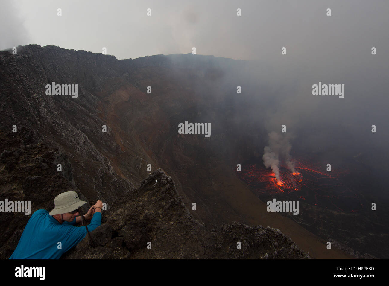 A tourist looks over the crater of Nyiragongo Volcano in the Virunga National Park, DRC to the active lava lake - Stock Image
