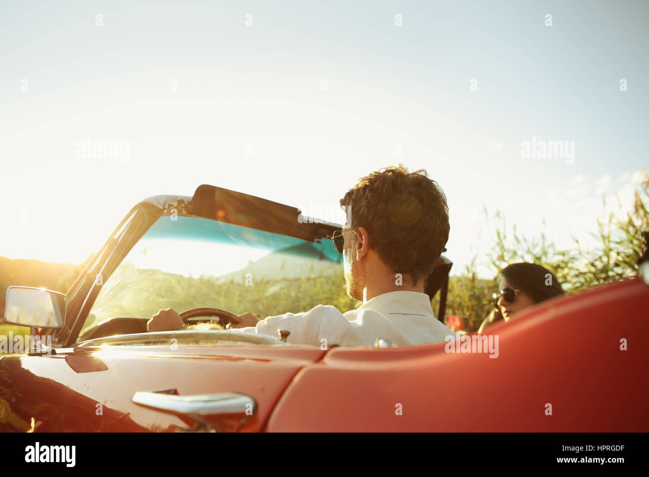 Couple driving convertible car enjoying a summer day at sunset Stock Photo